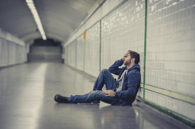 man-lost-in-depression-sitting-on-ground-street-subway-tunnel